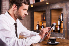 Surfing the net in bar. Side view of handsome young man in shirt and tie sitting at the bar counter and working on digital tablet Stock Images