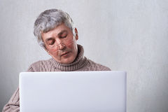 Surfing the net at home. Pensive mature man wearing eyeglasses and casual sweater reading a book on his laptop while siting at hom. E having dreaming expression Stock Photos