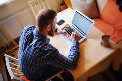 Surfing the net in office. Confident young man working on laptop and smiling while sitting at his working place in office.  Royalty Free Stock Photography