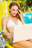 Surfing the net by the poolside. Stock Photography