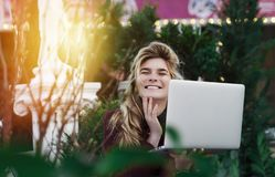 Thoughtful young woman in glasses using a computer, sitting on a bench in a city park. The concept of time is online and work in stock photos