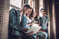 Surfing the net together. Group of happy young people working together and looking at laptop while sitting at the window sill. Indoors royalty free stock image