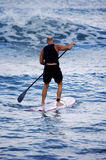 Surfing with Oar. Tom Thayer taking a break and surfing with an oar stock photo