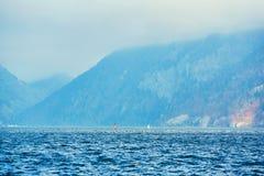Surfing p? sj?landskap och dimmiga berg p? bakgrund Mansurfare p? br?det med att segla att sv?va p? sj?n arkivfoto