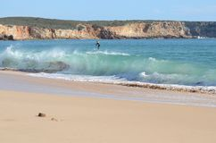 Surfing on a paddleboard. Beach with paddle boarder surfing waves in Portugal royalty free stock photo
