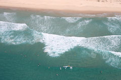 Surfing Paradise Aerial. Overhead Aerial perspective view of surfers catching waves in pristine water. One rider is on the wave, the others are waiting. Main stock images