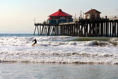 Surfing by Pier. Surfer at Huntington Beach Pier Stock Photos