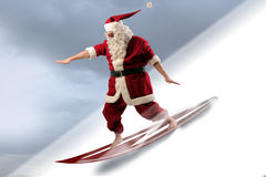 Surfing Santa. Santa is surfing or sowboarding down a snowy hill royalty free stock photo