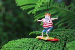 Surfing Santa Claus on Norfolk pine tree. Surfing Santa-Claus on Norfolk pine tree, Hawaii stock photo