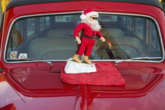 Surfing Santa Clause on a vintage red car hood, California, USA stock photography