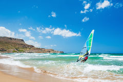 Surfing on the sea coast. Tropical beach with turquoise water and big waves. Crete island, Greece Stock Photos