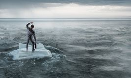 Surfing sea on ice floe. Mixed media. Businessman on ice block floating in sea . Mixed media Royalty Free Stock Image