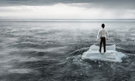 Surfing sea on ice floe. Mixed media. Businessman on ice block floating in sea . Mixed media Stock Photo