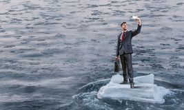 Surfing sea on ice floe. Mixed media. Businessman on ice block floating in sea and making selfie. Mixed media . Mixed media Stock Photography