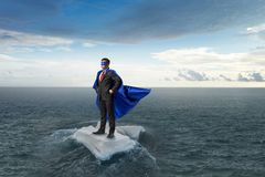 Surfing sea on ice floe. Mixed media. Businessman super hero on ice block floating in sea . Mixed media Stock Photos