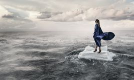 Surfing sea on ice floe. Mixed media. Businesswoman on ice block floating in sea . Mixed media Royalty Free Stock Photo