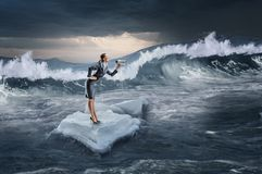 Surfing sea on ice floe. Mixed media. Businesswoman on ice block floating in sea . Mixed media Stock Photo