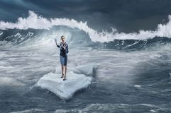 Surfing sea on ice floe. Mixed media. Businesswoman on ice block floating in sea . Mixed media Royalty Free Stock Photography