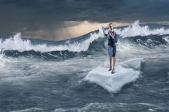 Surfing sea on ice floe. Mixed media. Businesswoman on ice block floating in sea . Mixed media Royalty Free Stock Images
