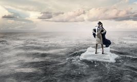 Surfing sea on ice floe. Mixed media. Businesswoman on ice block floating in sea . Mixed media Royalty Free Stock Image
