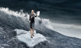 Surfing sea on ice floe. Mixed media. Businesswoman on ice block floating in sea . Mixed media Stock Photography