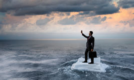 Surfing sea on ice floe. Young businessman floating on ice block in sea. Mixed media Stock Image