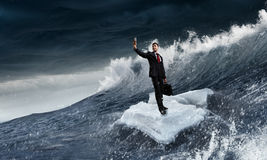 Surfing sea on ice floe. Young businessman floating on ice block in sea. Mixed media Royalty Free Stock Images