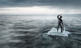 Surfing sea on ice floe. Young businessman floating on ice block in sea. Mixed media Stock Images