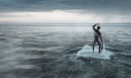 Surfing sea on ice floe. Young businessman floating on ice block in sea. Mixed media Stock Photos