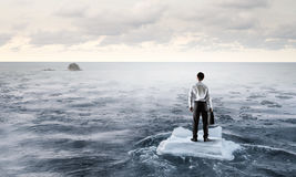Surfing sea on ice floe. Young businessman floating on ice block in sea. Mixed media Royalty Free Stock Photo