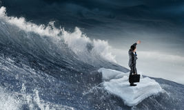 Surfing sea on ice floe. Young businessman floating on ice block in sea. Mixed media Royalty Free Stock Photography