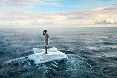 Surfing sea on ice floe. Young businesswoman floating on ice block in sea. Mixed media Royalty Free Stock Photos