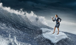 Surfing sea on ice floe. Young businesswoman floating on ice block in sea. Mixed media Royalty Free Stock Image