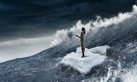 Surfing sea on ice floe. Young businesswoman floating on ice block in sea. Mixed media Stock Images