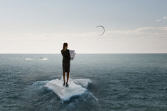 Surfing sea on ice floe. Young businesswoman floating on ice block in sea. Mixed media Stock Photos