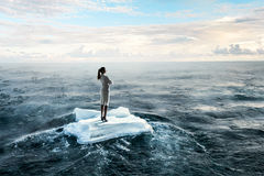 Surfing sea on ice floe. Young businesswoman floating on ice block in sea. Mixed media Stock Photo