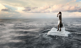 Surfing sea on ice floe. Young businesswoman floating on ice block in sea. Mixed media Stock Image