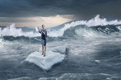 Surfing sea on ice floe. Young businesswoman floating on ice block in sea. Mixed media Royalty Free Stock Photo
