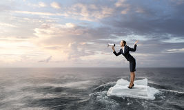 Surfing sea on ice floe. Young businesswoman floating on ice block in sea. Mixed media Stock Photography