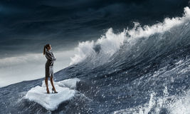 Surfing sea on ice floe. Young businesswoman floating on ice block in sea. Mixed media Royalty Free Stock Photography