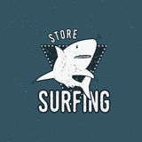 Surfing store emblem design. Shark on a triangle sheld. Retro rough style. Surfing logo template isolated on blue. Background. Vector summer insignia Royalty Free Stock Image