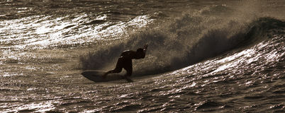 Surfing at Sunset. A surfer is riding a wave by sunset along beautiful Oahu, Hawaii North Shore stock images