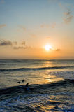 Surfing at Sunset. Backlight Silhouette Surfer in the Ocean at Sunset Royalty Free Stock Photos