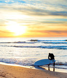 Surfing at sunset. Surfer getting ready for surfing on the beach at sunset Royalty Free Stock Image