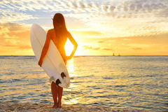 Surfing surfer girl looking at ocean beach sunset Stock Images