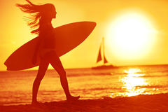 Surfing surfer woman babe beach fun at sunset. Girl walking in sunshine in warm evening sun holding surfboard. Water sport summer vacation travel concept Stock Photos