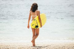 Surfing surfer woman girl walking holding surfboard. Water sport summer vacation travel concept. royalty free stock photography