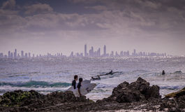 Surfing at Surfers Paradise. Surfers Paradise, Australia on August 16, 2016: Surfers enjoying the waves at snapper rocks with the skyline of Surfers paradise in Royalty Free Stock Photos