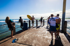 Surfing People Waves Pier. Surfers ready to jump into ocean off pier to surf morning ocean waves at surf-city Durban South Africa royalty free stock photography