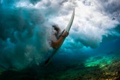 Surfing. Underwater shot of the male surfer trying to get out from the broken wave stock photo